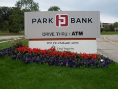 Flowers Beneath Park Bank Sign